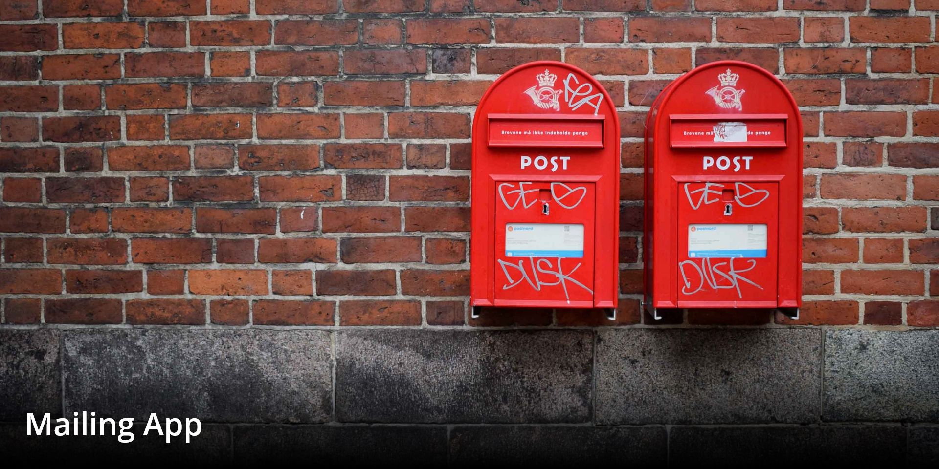 two post boxes on a brick wall